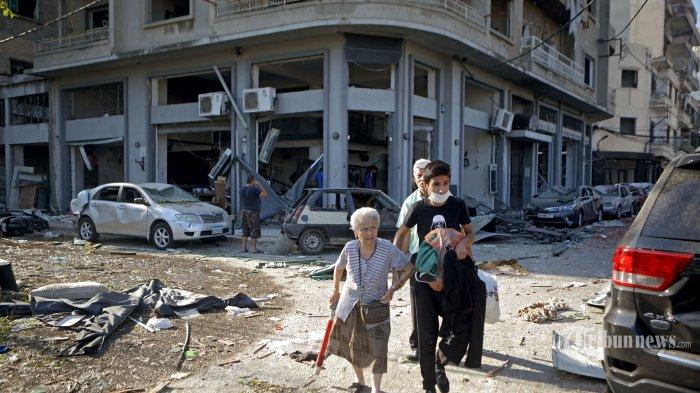 Warga mengungsi dari sekitar lokasi ledakan dahsyat yang terjadi sehari sebelumnya di kawasan pelabuhan, di Kota Beirut, Lebanon, Rabu (5/8/2020) pagi waktu setempat. Dua ledakan besar terjadi di Kota Beirut menyebabkan puluhan orang meninggal, ribuan lainnya luka-luka, dan menimbulkan berbagai kerusakan pada bangunan di kawasan ledakan hingga radius puluhan kilometer. Penyebab ledakan masih dalam penyelidikan pihak yang berwenang. AFP/Patrick Baz