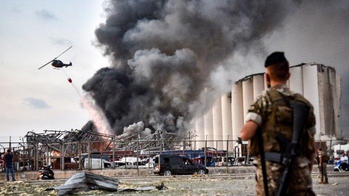 Ilustrasi. Tentara Lebanon berdiri di sekitar lokasi ledakan, sementara sebuah helikopter memadamkan api di lokasi ledakan di pelabuhan ibukota Lebanon, Beirut pada 4 Agustus 2020.
