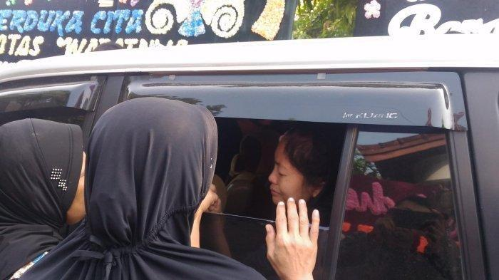 Linda Herawati (42) korban selamat dalam kecelakaan di Tol Cipali berurai air mata mengiringi ambulans yang membawa jenazah suami dan dua anaknya, Senin (29/7/2019). Tribunlampung.co.id/Hanif