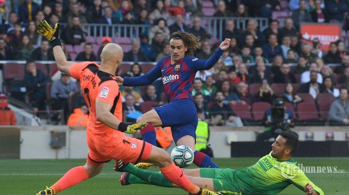 Pemain depan FC Barcelona asal Prancis, Antoine Griezmann (tengah) berusaha mengecoh penjaga gawang Eibar asal Serbia, Marko Dmitrovic (kiri) dalam laga lanjutan Liga Spanyol di Stadion Camp Nou, Barcelona, Spanyol, Sabtu (22/2/2020) malam WIB. FC Barcelona berhasil mengalahkan Eibar dengan skor 5-0, empat gol di antaranya dilesakkan Lionel Messi. AFP/Josep Lago