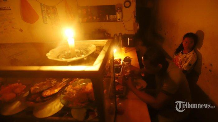 Warga beraktifitas menggunakan penerangan lilin dan lampu darurat, di wilayah Karet Tengsin Jakarta, Minggu malam (4/8/2019). Aliran listrik di Banten, Jabodetabek hingga Bandung terputus akibat adanya gangguan pada sejumlah pembangkit di Jawa. TRIBUNNEWS/HERUDIN