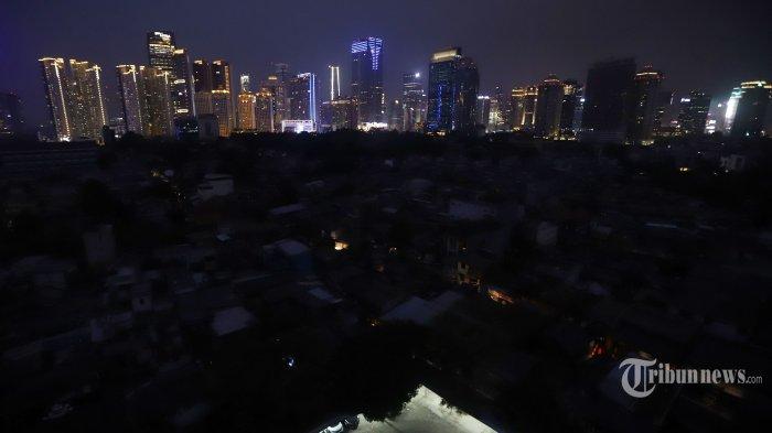 Permukiman warga Jakarta difoto dari Rusun Karet Tengsin terlihat gelap gulita hanya gedung perkantoran dan apartemen yang terang, Minggu malam (4/8/2019). Aliran listrik di Banten, Jabodetabek hingga Bandung terputus akibat adanya gangguan pada sejumlah pembangkit di Jawa. TRIBUNNEWS/HERUDIN
