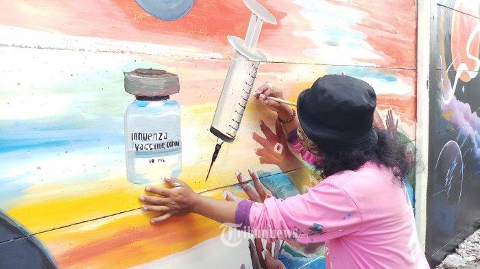 PESAN MORAL LEWAT MURAL - Seniman lukis mural sedang mengekspresikan karyanya di tembok pembatas kampung di wilayah Tanah Tinggi, Kota Tangerang, Selasa (22/12/2020). Mereka melukis tentang berbagai hal, salah satunya lukisan tentang orang memakai masker dan mencuci tangan, lewat lukisan ini mereka ingin mengedukasi dan meningkatkan kesadaran masyarakat untuk mengikuti anjuran pemerintah dalam mematuhi protokol kesehatan agar terhindar dari paparan Covid-19. WARTA KOTA/NUR ICHSAN
