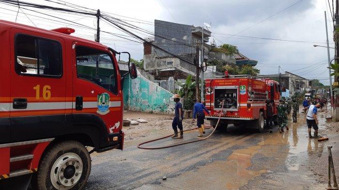 Dua armada pemadam kebakaran pembawa air diterjunkan ke Perumahan Pondok Gede Permai, Bekasi, Jawa Barat, untuk membantu membersihkan lumpur, Minggu (21/2/2021).