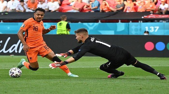Penyerang Belanda Donyell Malen (kiri) berebut bola dengan kiper Republik Ceko Tomas Vaclik pada pertandingan sepak bola babak 16 besar UEFA EURO 2020 antara Belanda dan Republik Ceko di Puskas Arena di Budapest pada 27 Juni 2021.