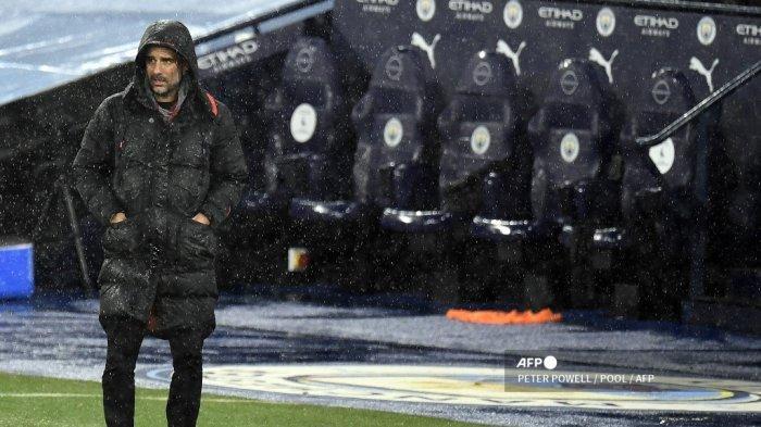 Manajer Manchester City Spanyol Pep Guardiola berdiri di tengah hujan selama pertandingan sepak bola Liga Utama Inggris antara Manchester City dan Newcastle United di Stadion Etihad di Manchester, Inggris barat laut, pada 26 Desember 2020. PETER POWELL / POOL / AFP