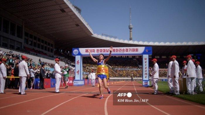 Ri Kang Bom dari Korea Utara melewati garis finis 'Mangyongdae Prize International Marathon' tahunan di stadion Kim Il Sung di Pyongyang pada 7 April 2019. Dua kali lebih banyak orang asing dibandingkan tahun lalu berkumpul di Pyongyang untuk maraton tahunan kota, tur kata perusahaan, karena ketegangan yang berkurang menyebabkan jumlah pengunjung meningkat di Korea Utara yang terisolasi. Acara tersebut - bagian dari perayaan ulang tahun kelahiran pendiri Kim Il Sung pada tahun 1912 - adalah puncak dari kalender pariwisata Korea Utara dan menawarkan kesempatan untuk berlari atau jogging di jalan-jalan kota yang dikontrol ketat.