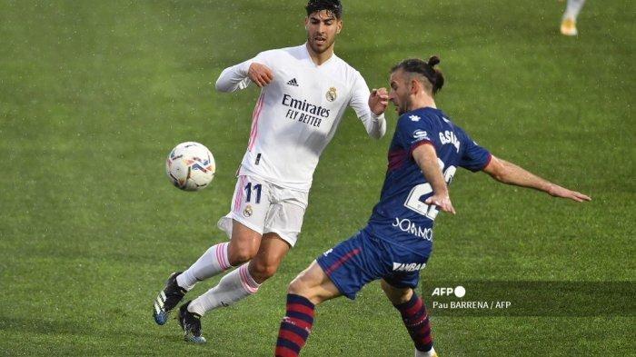 Gelandang Spanyol Real Madrid Marco Asensio (kiri) menantang bek Uruguay Huesca Gaston Silva selama pertandingan sepak bola liga Spanyol antara SD Huesca dan Real Madrid di stadion El Alcoraz di Huesca pada 6 Februari 2021. Pau BARRENA / AFP