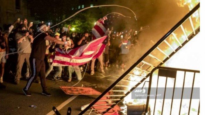 Massa demonstran melemparkan bendera AS ke arah kobaran api dalam unjuk rasa memprotes kasus tewasnya George Floyd di luar Gedung Putih, Washington DC, AS, Minggu (31/5/2020).