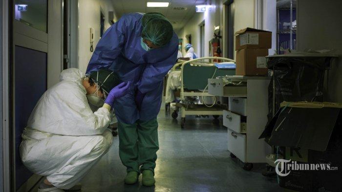 Seorang tenaga medis menghibur rekannya saat pergantian jam kerja di RS Cremona, Lombardy, tenggara Milan, Jumat (13/3/2020). Italia adalah negara dengan tingkat pandemi virus corona tertinggi di dunia mengalahkan Cina, dengan jumlah kasus positif di atas 85 ribu jiwa dan lebih dari 9 ribu orang meninggal dunia hingga 29 Maret 2020. Ganasnya penyebaran Covid-19 di Italia membuat tenaga medis yang terbatas mulai kewalahan. AFP/PAOLO MIRANDA