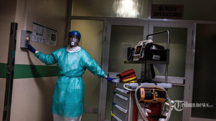 Seorang tenaga medis menggunakan alat pelindung diri membawa alat kesehatan darurat saat akan menangani penderita Covid-19 di RS Cremona, Lombardy, tenggara Milan, Jumat (13/3/2020). Italia adalah negara dengan tingkat pandemi virus corona tertinggi di dunia mengalahkan Cina, dengan jumlah kasus positif di atas 85 ribu jiwa dan lebih dari 9 ribu orang meninggal dunia hingga 29 Maret 2020. Ganasnya penyebaran Covid-19 di Italia membuat tenaga medis yang terbatas mulai kewalahan. AFP/PAOLO MIRANDA