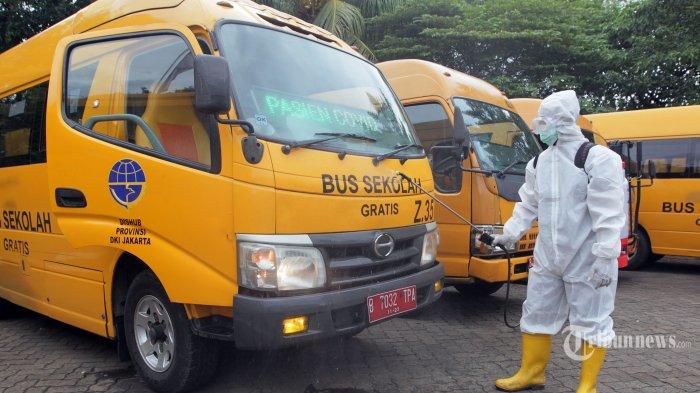 Petugas Kebersihan Bus (PKB) saat melakukan penyemprotan cairan disinfektan pada salah satu bus usai digunakan untuk mengangkut pasien Covid 19 di Pool Bus Sekolah DKI Jakarta, Kramat Jati, Jakarta Timur, Selasa (5/1/2020). Unit Pelayanan Angkutan Sekolah (UPAS) melakukan dua tahap sterilisasi yaitu penyemprotan cairan disinfektan dan pengasapan bakteri. UPAS mengerahkan 16 Armada bus sekolah dari 176 bus sekolah untuk mengantar dan menjemput pasien positif Covid menuju rumah sakit rujukan di Jakarta. Tribunnews/Jeprima