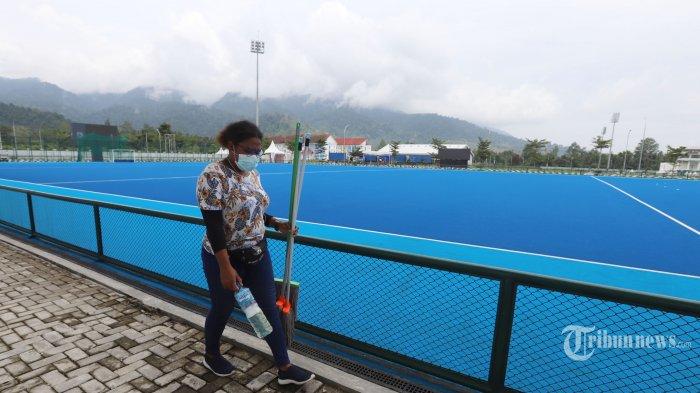 Pekerja usai membersihkan Venue Hockey Outdoor yang akan digunakan pada ajang olahraga 4 tahunan sekali PON XX Papua di Kampung Doyo Lama, Kabupaten, Sentani, Jayapura, Papua, Jumat (24/9/2021). Event tersebut akan berlangsung pada 4 hingga 12 Oktober 2021. (Tribunnews/Jeprima)