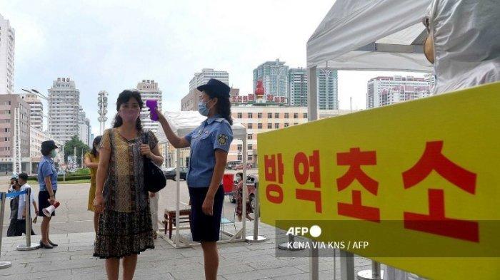Gambar tak bertanggal yang dirilis dari Kantor Berita Pusat Korea (KCNA) resmi Korea Utara pada 29 Agustus 2020 ini menunjukkan seorang pegawai stasiun memeriksa suhu tubuh penumpang sebagai langkah untuk mencegah penyebaran virus corona COVID-19 di Pyongyang.