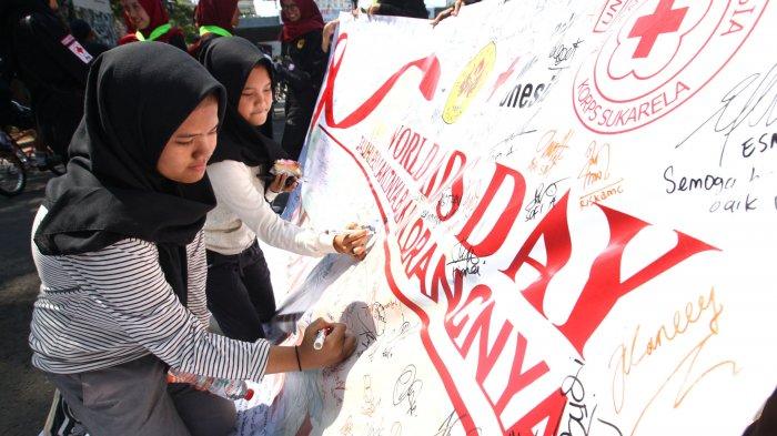 Warga membubuhkan tandatangan pada kain bertuliskan World AID Day Jauhi Penyakitnya Bukan Orangnya yang dibentangkan oleh anggota KSR Unpas di arena Car Free Day (CFD) Dago, Jalan Ir H Djuanda, Kota Bandung, Jawa Barat, Minggu (1/12/2019). Kegiatan dalam rangka memperingati Hari AIDS Sedunia yang jatuh pada 1 Desember itu mengajak kepada masyarakat untuk meningkatkan kepedulian dalam menghentikan epidemi HIV/AIDS yang di Indonesia jumlah infeksi HIV berdasarkan data Juni 2019 sebanyak 349.882 orang. Serta mengajak untuk menjauhi penyakit HIV/AIDS dan tidak menjauhi atau bahkan mengucilkan penderitanya. Tribun Jabar/Gani Kurniawan (Tribun Jabar/Gani Kurniawan)