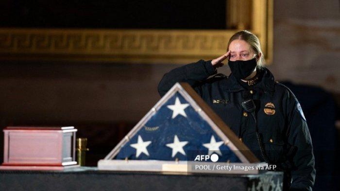 Seorang Petugas Polisi Capitol memberi penghormatan sebelum upacara untuk memperingati Petugas Polisi Capitol AS Brian D. Sicknick di Rotunda Capitol pada hari Rabu, 3 Februari 2021 di Washington DC.