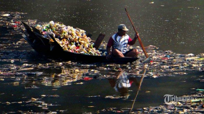 Seorang warga menggunakan perahu  mencari plastik bekas diantara sampah yang terbawa aliran Sungai Citarum dibawah Jembatan BBS, Batujajar, Kabupaten Bandung Barat, Kamis (11/06/2020). Bagi mereka waktu setelah turun hujan di wilayah Kota Bandung merupakan kesempatan untuk mengais sampah plastik yang banyak terbawa aliran air sungai mengarah ke Jembatan BBS. (TRIBUN JABAR/Zelphi)