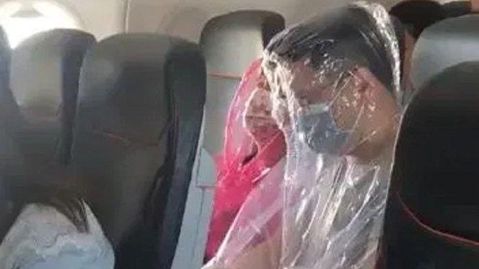Dua penumpang pesawat terlihat menutupi seluruh tubuhnya menggunakan plastik untuk menghindari virus corona.