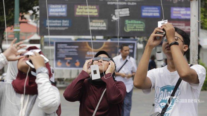 Sejumlah warga mengamati proses terjadinya gerhana matahari parsial atau sebagian dengan menggunakan kacamata matahari yang disediakan oleh Jogja Astro Club di halaman Masjid Gede Kauman, Kota Yogyakarta, Kamis (26/12/2019) siang. Hanya di sebagian wilayah Sumatera dan Kalimantan masyarakat dapat menyaksikan fenomena alam gerhana matahari cincin. Tribun Jogja/Hasan Sakri Ghazali