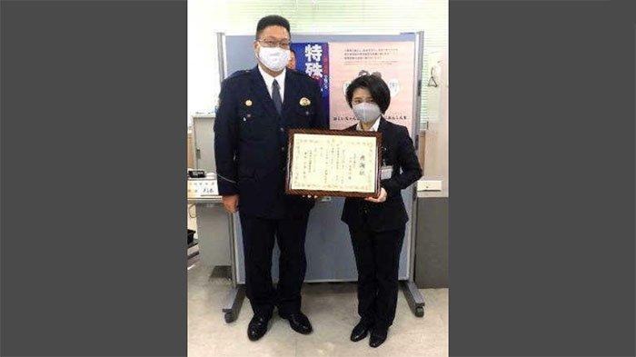 Mihoko Nakaji (kanan), menerima sertifikat penghargaan kepolisian Kawanisi diserahkan oleh Kepala Polisi, Naoyuki Sugimoto (kiri).