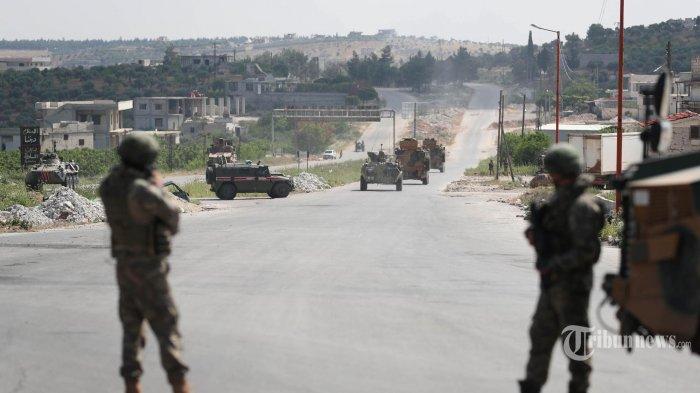FILE - Tentara Turki mengawasi ketika kendaraan militer patroli Rusia-Turki melewati jalan raya M4 di pinggiran kota Ariha yang dikuasai pemberontak di provinsi Idlib barat laut Suriah pada 7 Mei 2020. - (Foto oleh Omar HAJ KADOUR / AFP )