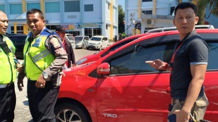 Mobil Agya merah, diduga pelaku penembakan mahasiswa UBL. Kaca samping bagian kiri mobil terlihat berlubang setelah tertembus peluru. Tribun Lampung/Beni Yulianto