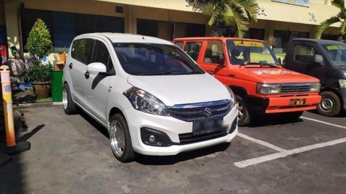 Mobil jenis Suzuki Ertiga warna putih diamankan dan berada di Mapolresta Denpasar pada Kamis (7/8/2019). Menurut keluarga korban pembunuhan, membenarkan mobil tersebut yang digunakan Ni Putu Yuniawati pada Senin (5/8/2019) malam. Tribun Bali/Firizqi Irwan