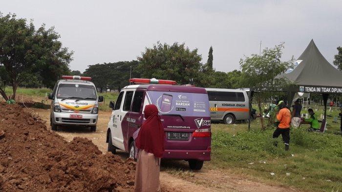 Mobil jenazah antre untuk memakamkan jenazah dengan SOP Covid-19 di TPU Tegal Alur, Kalideres, Jakarta Barat, Minggu (5/4/2020).