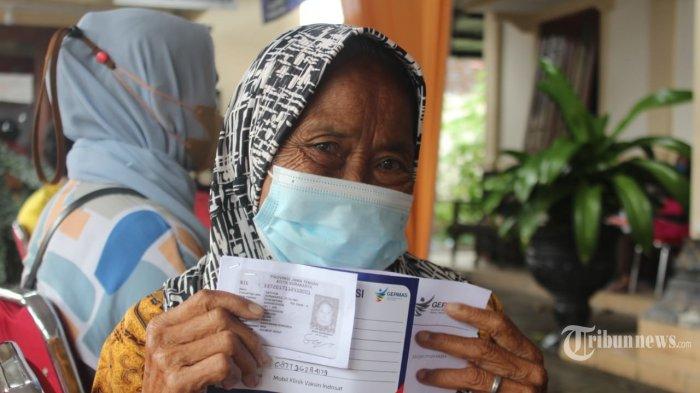Aarga Solo menunjukan data diri saat akan melakukan vaksinasi yang dibantu dengan fasilitas Mobil Klinik Indosat Ooredoo, Sabtu (26/6/2021). Mobil klinik Indosat Ooredoo dengan teknologi 5G membantu dalam mempercepat proses vaksinasi 124 warga lansia dan pra lansia di kelurahan Mojosongo kota Solo. TRIBUNNEWS.COM/HO