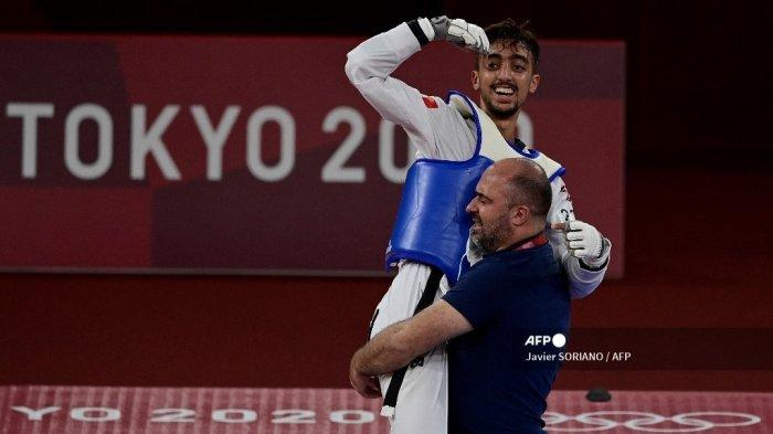 Pemain Tunisia Mohamed Khalil Jendoubi (Biru) merayakan dengan pelatihnya setelah memenangkan pertandingan semifinal taekwondo -58kg putra melawan Jang Jun (Merah) dari Korea Selatan selama Olimpiade Tokyo 2020 di Makuhari Messe Hall di Tokyo pada 24 Juli 2021.
