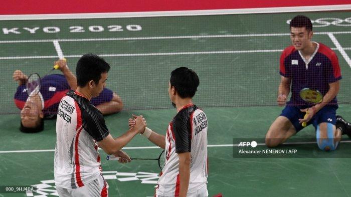Mohammad Ahsan (tengah) dari Indonesia dan Hendra Setiawan dari Indonesia bersimpati setelah kalah dalam pertandingan semifinal bulu tangkis ganda putra ketika Lee Yang (kiri) dari Taiwan melakukan selebrasi di sebelah Wang Chi-lin (kanan) dari Taiwan selama Olimpiade Tokyo 2020 di Musashino Forest Sports Plaza di Tokyo pada 30 Juli 2021.