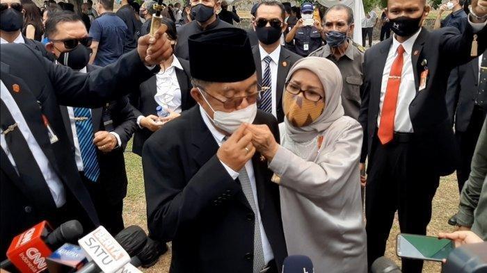Mufidah Jusuf Kalla memperbaiki masker suaminya, Jusuf Kalla, saat tengah diwawancarai awak media di TMP Kalibata, Jakarta Selatan, Kamis (10/9/2020).
