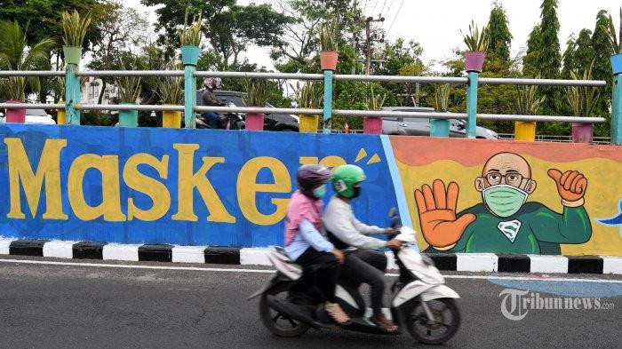 Pengendara motor melintas di dekat dinding bermural di kawasan Ketabang Kali, Kota Surabaya, Jawa Timur, Minggu (18/10/2020). Mural di sepanjang dinding viaduk itu sebagai imbauan kepada masyarakat untuk menerapkan protokol kesehatan pencegahan penularan Covid-19. Surya/Ahmad Zaimul Haq