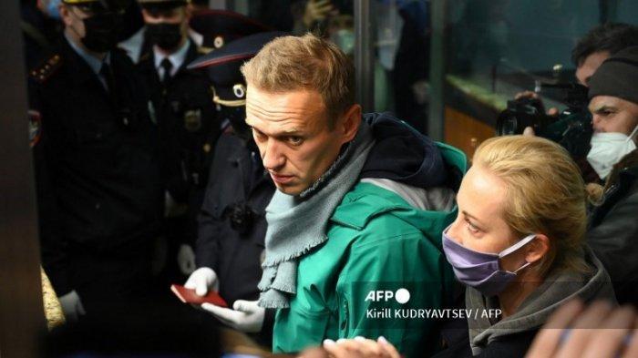 Pemimpin oposisi Rusia Alexei Navalny dan istrinya Yulia terlihat di titik pemeriksaan paspor di bandara Sheremetyevo Moskow pada 17 Januari 2021. Polisi Rusia menahan kritikus Kremlin Alexei Navalny di bandara Moskow tak lama setelah dia mendarat dalam penerbangan dari Berlin, seorang jurnalis AFP di tempat kejadian berkata.