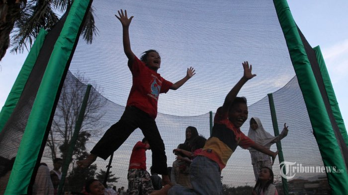 Sejumlah anak bermain trampolin sambil mengisi waktu berbuka puasa, di taman Bale Rancamanyar pinggir Sungai Citarum, Jalan Cilebak, Desa Rancamanyar, Kecamatan Baleendah, Kabupaten Bandung, Minggu (27/5/2018).  Selama Ramadan, taman di bantaran Sungai Citarum yang dibagun Balai Besar Wilayah Sungai (BBWS) Citarum itu menjadi tempat favorit warga sekitar untuk ngabuburit atau menunggu waktu berbuka puasa. (TRIBUN JABAR/GANI KURNIAWAN)