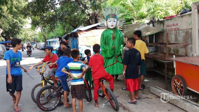 Sekumpulan anak-anak berkerumun menyaksikan pengamen ondel-ondel yang sedang beraksi di Jalan Kampung Duri Oasar, Tambira, Jakarta Barat, Jumat (3/4/2020). Padahal aktifitas mereka itu dapat mengundang serangan wabah Covid-19. (Wartakota/Nur Ichsan)