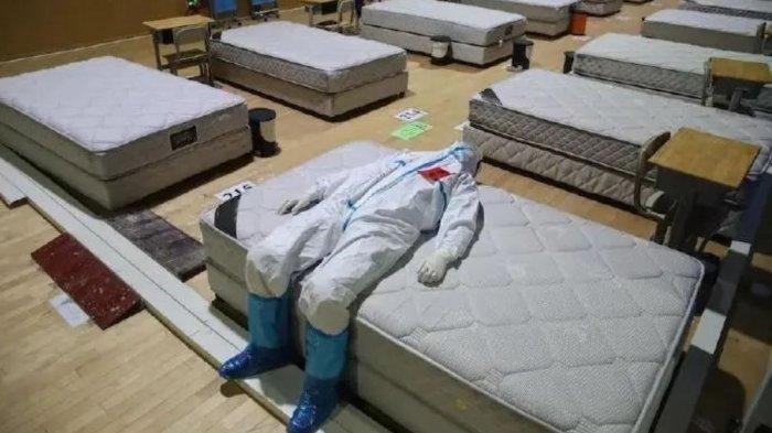 Foto seorang dokter di Wuchang yang berbaring dengan pakaian pelindung yang lengkap di kamar penuh dengan kasur kosong yang merupakan bekas rumah sakit pasien virus corona.