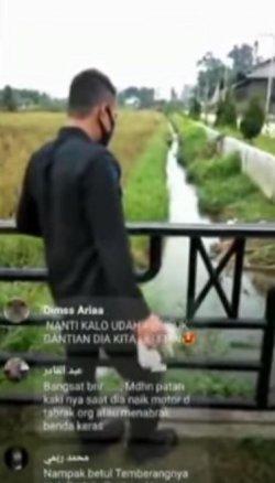 Tangkapan layar dari video viral seorang anggota Polri yang diduga berasal dari satuan Brimob melempar anak kucing ke sebuah parit.