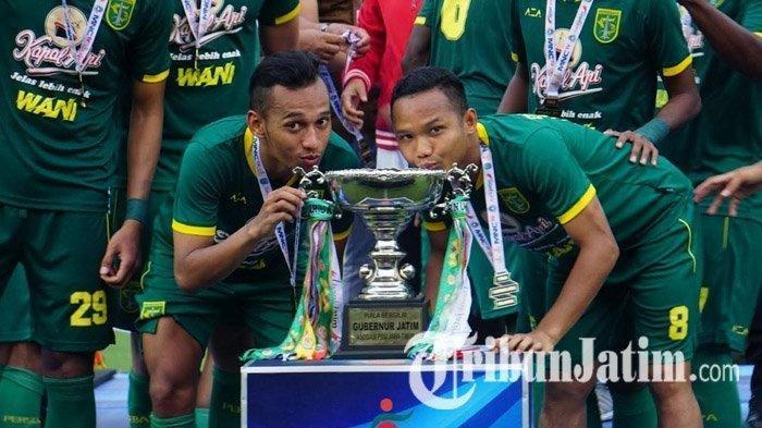 Pemain Persebaya Surabaya, Oktafianus Fernando (kanan) mencium trofi juara Piala Gubernur Jatim 2020. Dia membuktikan dengan guyonan bisa mendekatkan seluruh pemain Persebaya Surabaya dan tetap berprestasi.