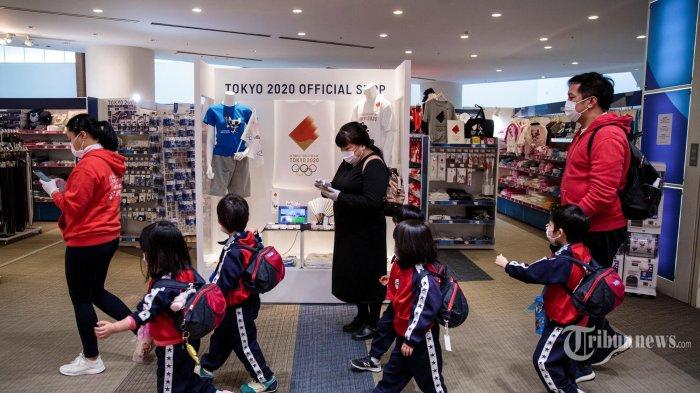 Anak-anak berjalan melewati toko resmi Tokyo 2020 di Tokyo. Sehari setelah keputusan bersejarah untuk menunda Olimpiade Tokyo 2020. -  Penundaan yang belum pernah terjadi sebelumnya yaitu mengatur kembali Olimpiade Tokyo setelah keputusan bersejarah untuk menunda acara olahraga terbesar di dunia karena pandemi virus coronavirus COVID-19 yang telah mengunci sepertiga planet ini. (AFP/Behrouz MEHRI)