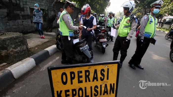 Petugas kepolisian Sat Lantas Restro Jakarta Barat melakukan Operasi Patuh Jaya 2017 di Jakarta, Jumat (12/5/2017). Operasi yang dilakukan selama kurang lebih dua minggu ini bertujuan untuk menekan angka pelanggaran lalu lintas. TRIBUNNEWS/IRWAN RISMAWAN