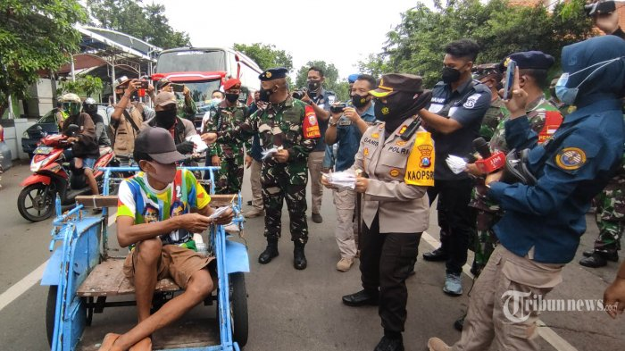 Komandan Lantamal V Surabaya, Laksamana Pertama TNI Mohamad Zaenal (kedua kiri) didampingi Kapolres Pelabuhan Tanjung Perak, AKBP Ganis Setyaningrum (kedua kanan) membagikan masker kepada pengguna jalan di depan Posko PPKM Mikro Kelurahan Ampel, Kota Surabaya, Jawa Timur, Senin (1/3/2021). Operasi yustisi yang digelar oleh TNI, Polri, dan Pemda itu juga menyiapkan tes Covid-19 bagi warga yang kedapatan tidak memakai masker. Surya/Ahmad Zaimul Haq