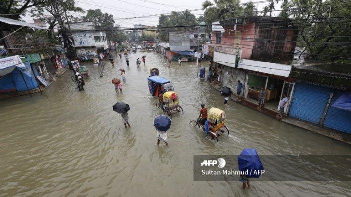 Dalam foto yang diambil pada 12 Juli 2020 ini, orang-orang berjalan melewati perairan banjir di Sunamgong, Bangladesh