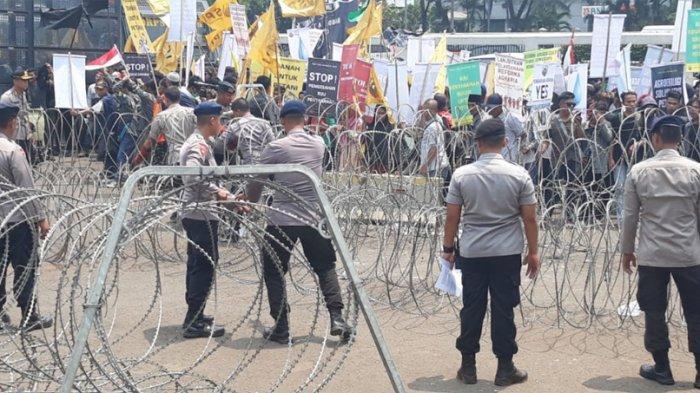 Sejumlah petugas kepolisian terlihat memasang pagar kawat berduri di depan Gedung DPR/MPR RI, Senayan, Jakarta Pusat, Selasa (24/9/2019).