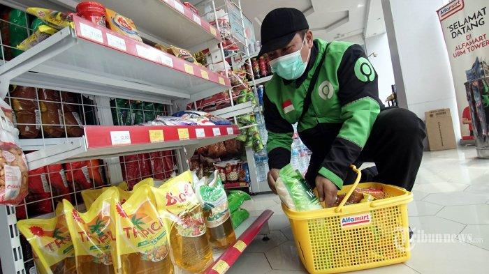 Mitra Gojek tengah berbelanja sembako di salah satu Gerai Alfamart, Senin (6/4/2020).