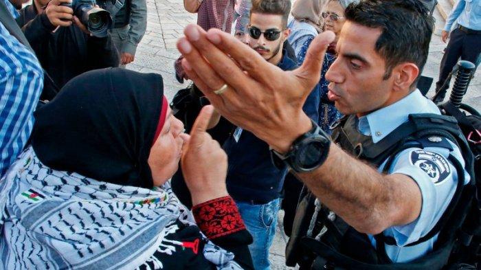 Seorang wanita Palestina berdebat dengan seorang anggota pasukan keamanan Israel ketika mereka membubarkan demonstrasi di luar Gerbang Damaskus di kota tua Yerusalem pada hari Selasa.