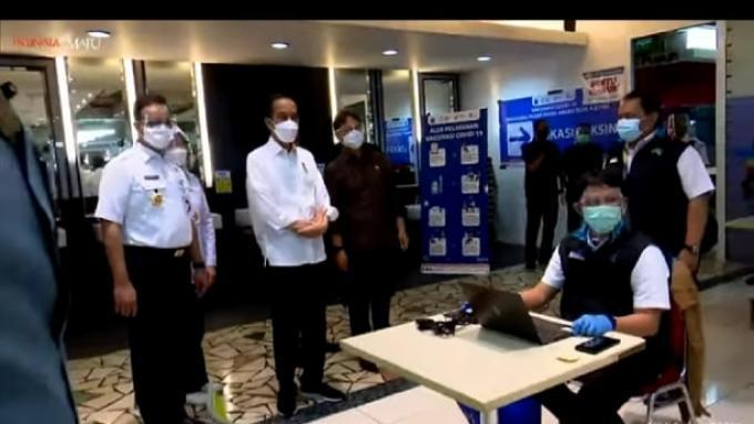 Presiden Joko Widodo (Jokowi) meninjau proses vaksinasi massal di Pasar Tanah Abang, Jakarta Pusat, pada Rabu, (17/2/2021).
