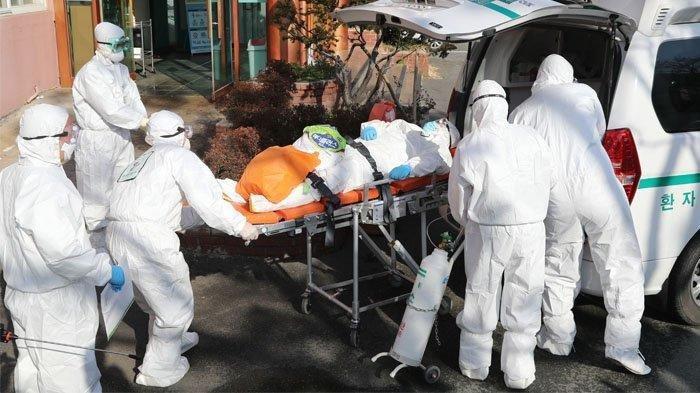 Para pekerja medis yang mengenakan alat pelindung memindahkan seorang tersangka pasien virus korona (C) ke rumah sakit lain