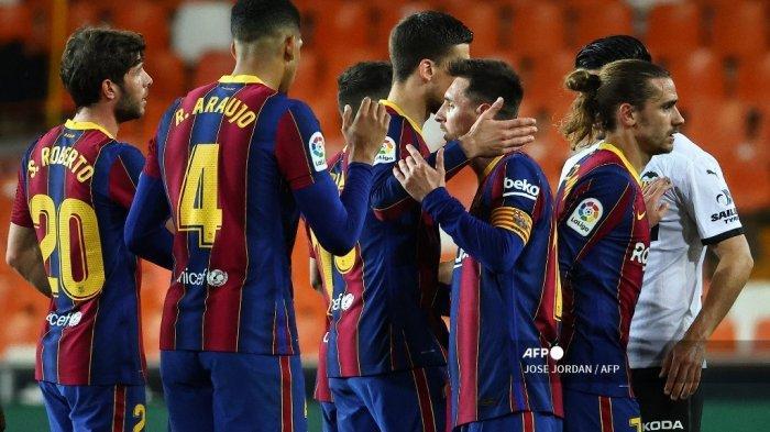 Para pemain Barcelona merayakan kemenangan mereka di akhir pertandingan sepak bola Liga Spanyol antara Valencia dan Barcelona di stadion Mestalla di Valencia pada 2 Mei 2021. JOSE JORDAN / AFP