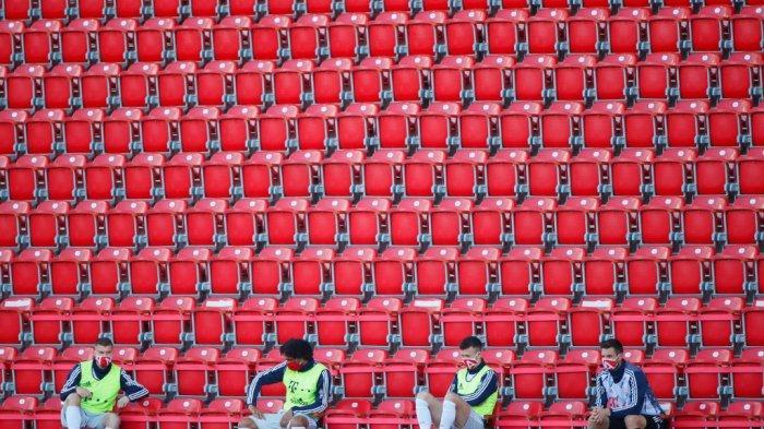 Pengganti Bayern Munich yang mengenakan topeng pelindung menjaga jarak sosial di tribun selama pertandingan sepak bola Bundesliga divisi satu Jerman FC Union Berlin v FC Bayern Munich pada 17 Mei 2020 di Berlin, Jerman saat musim dimulai kembali setelah absen selama dua bulan karena adanya novel pandemi coronavirus COVID-19.